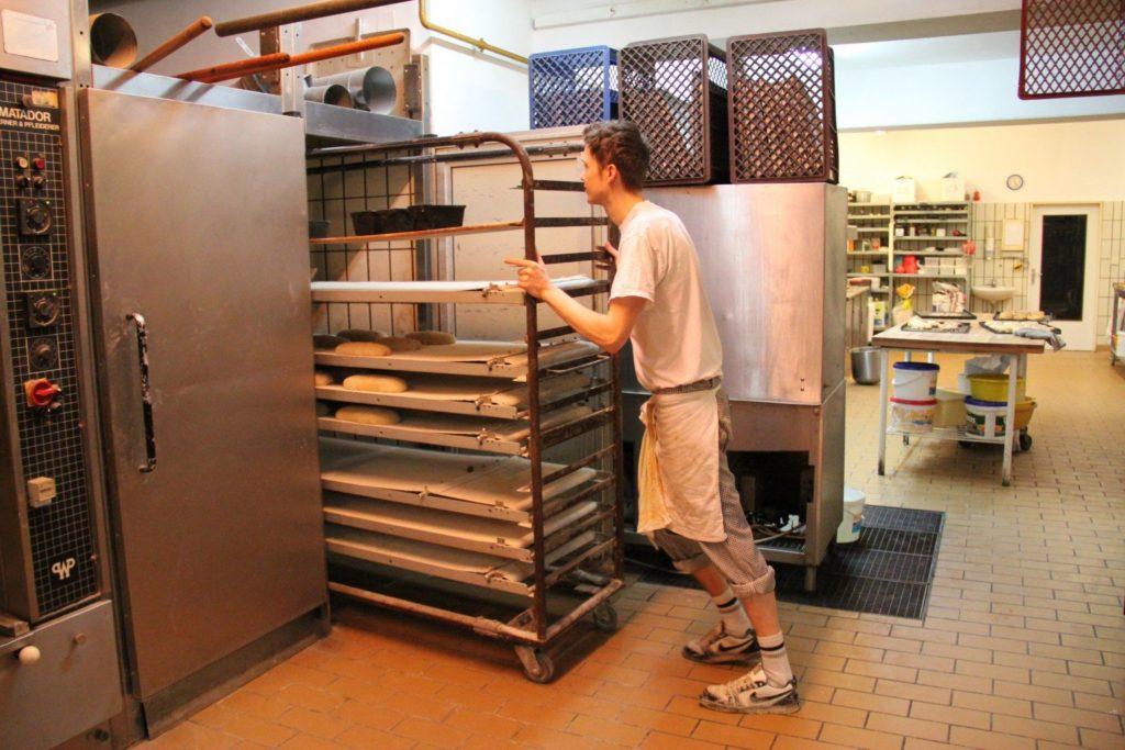 Geselle schiebt Brot in den Ofen